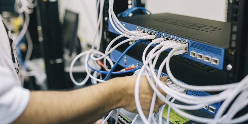 IT Support Engineer connects network switch cable