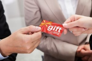 44306162 - close-up of businessperson hands giving gift card to other businessperson