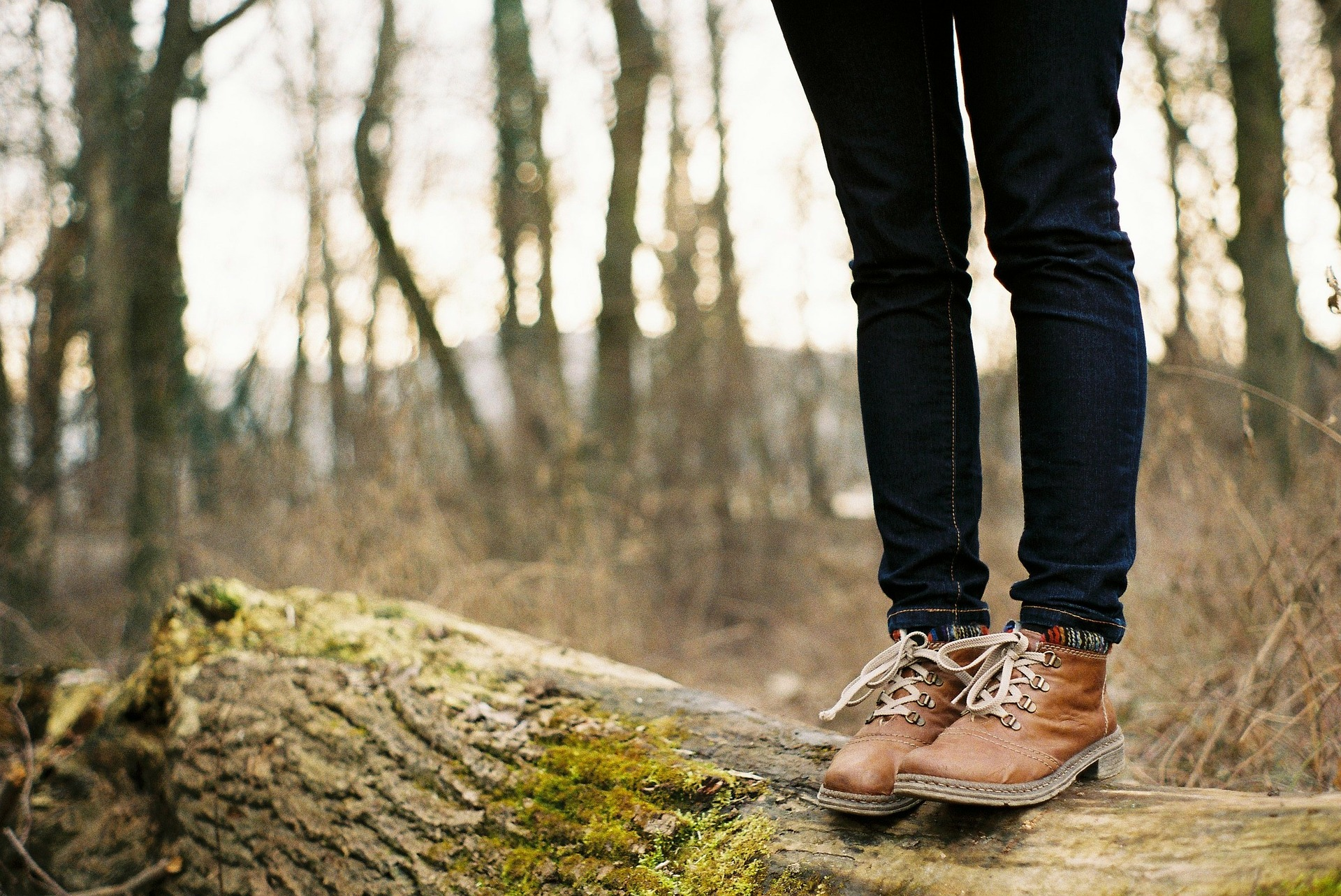 girl with boots standing on a log in the middle of the woods alone