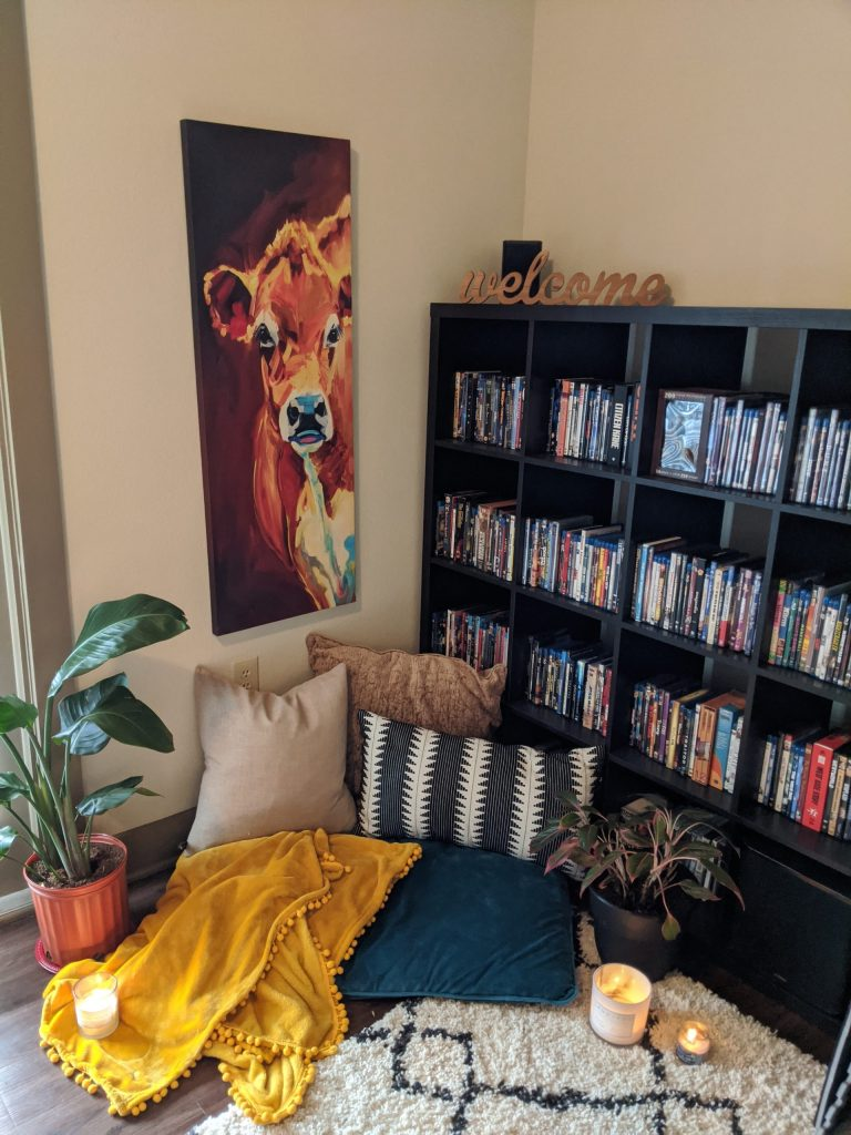 calm corner with cow and bookshelf and pillows on the floor