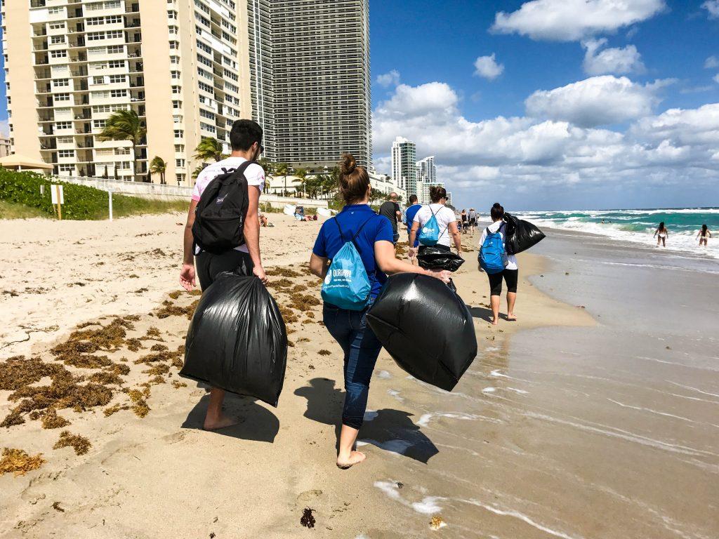 Volunteers-walking-on-beach-with-trash-2-1024x768