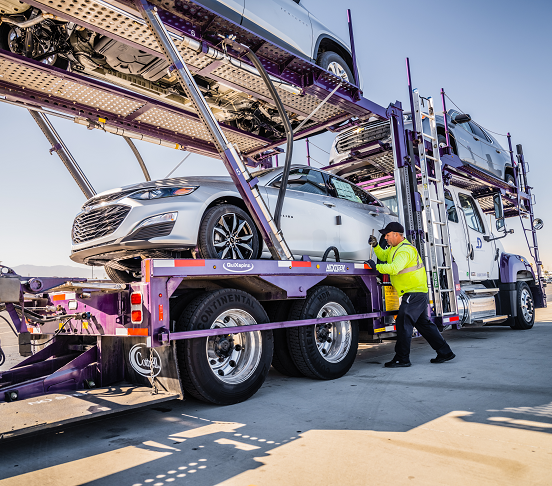 A specialist is working to lift a car to auto carriers