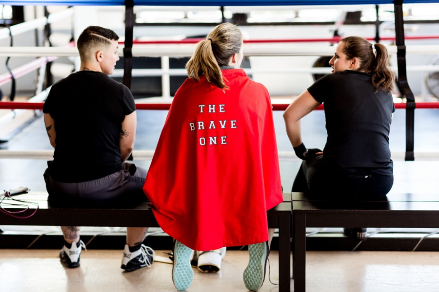 "Three women sit on a bench in a gym. The middle wears a red cape that reads ""The Brave One."""