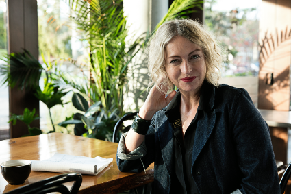 Linda Derschang poses in one of her restaurants, beside a cup of coffee and a notepad.