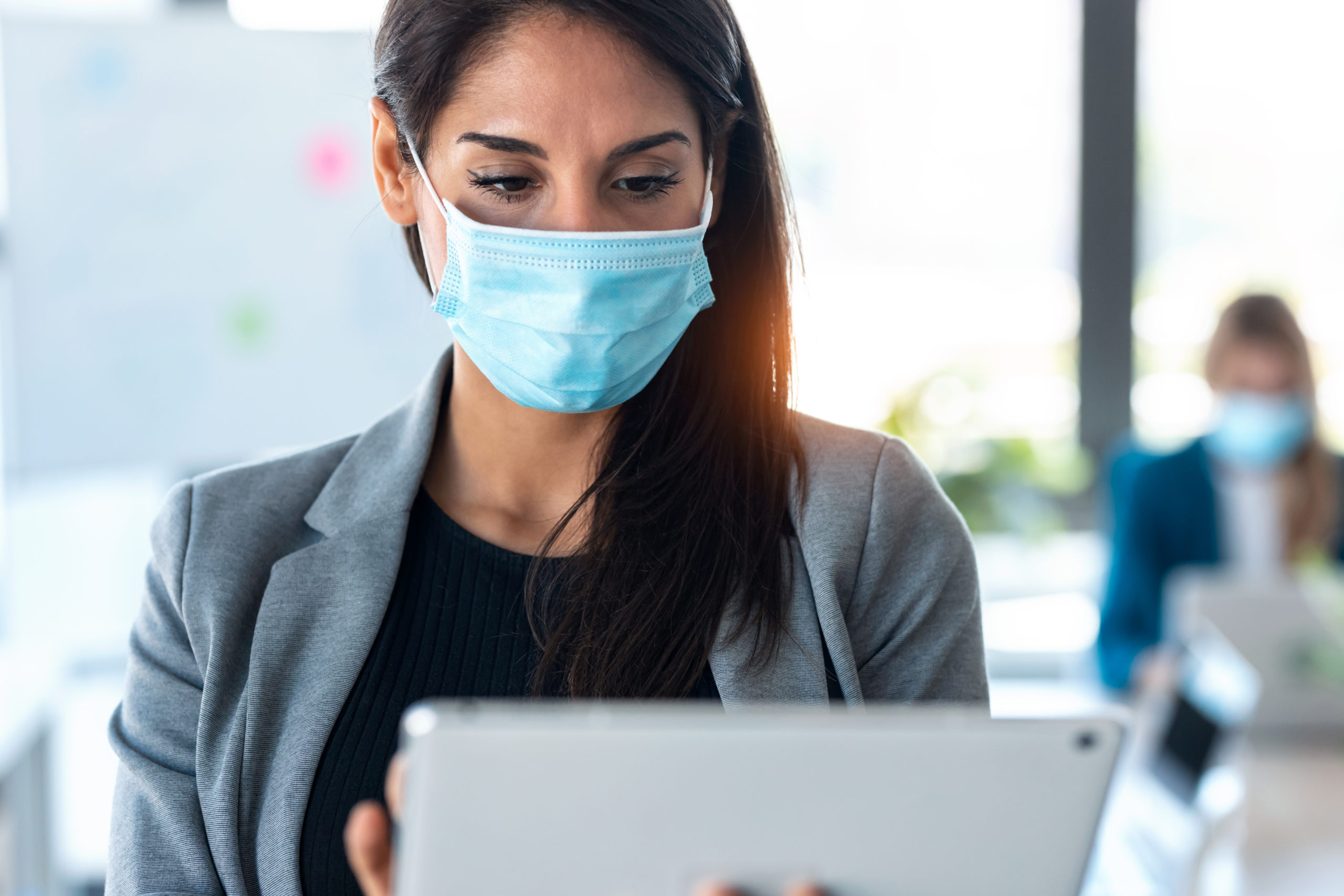 woman-wearing-a-hygienic-face-mask-while-work-with-XA93DW4-scaled