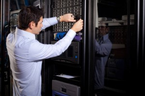 An IT technician is shown repairing data drives on a server network